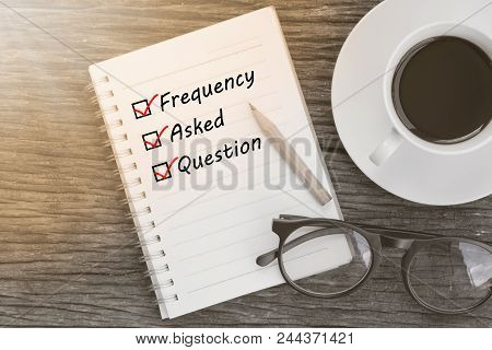 Frequency Asked Question And Check List Marks In Notebook With Glasses, Pencil And Coffee Cup On Woo