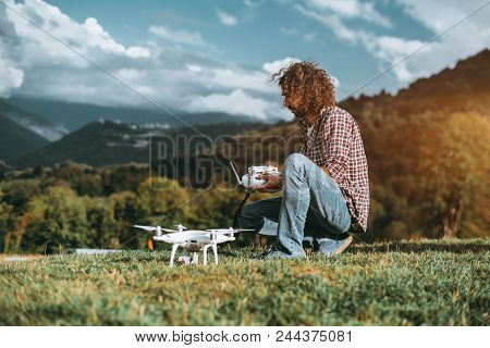 A Serious Bearded Hipster Man In A Checkered Shirt Is Sitting On The Grass Of A Mountain Meadow And