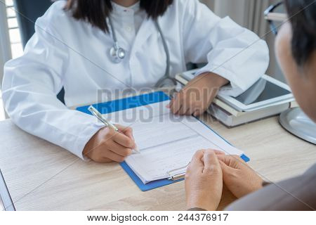 Healthcare Medical Concept. Asian Young Female Doctor Talking , Writing Prescription Clipboard With