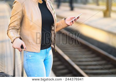 Commuter Using Smartphone In Train Station. Woman Buying Electronic Ticket With Mobile Phone In Plat
