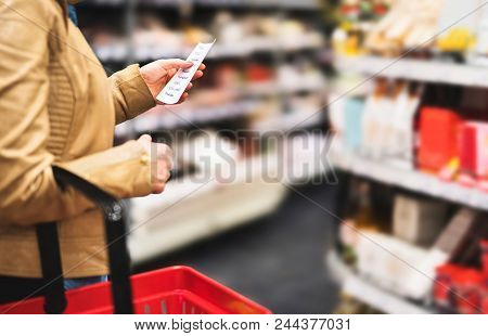 Reading Shopping List In Supermarket. Female Customer In Grocery Store With Budget, Plan Or Checklis