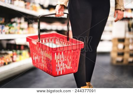 Woman Holding Shopping Basket And Walking In Grocery Store Aisle. Lady Buying Groceries And Food In