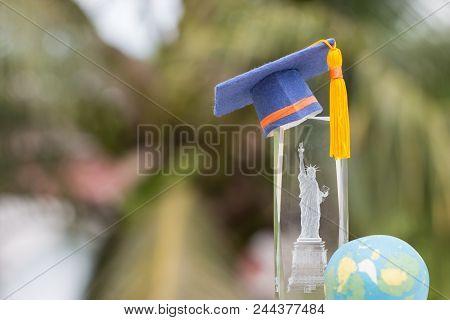 Learning Study International Abroad In America Concept: Graduate Cap On Blur Of Usa Statue Of Libert
