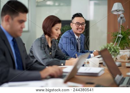 Working Meeting At Spacious Boardroom: Multi-ethnic Group Of Managers In Formalwear Sitting At Woode