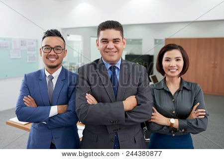 Smiling White Collar Workers In Formalwear Standing At Spacious Boardroom With Arms Crossed And Look