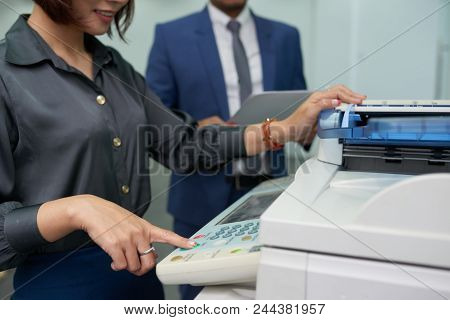 Close-up Shot Of Smiling Office Assistant Using Multi-function Printer In Order To Make Copy Of Docu