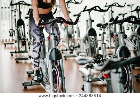 Feet Of An Attractive Young Girl Training On Bike In Gym. Fitness Woman On Bicycle Doing Spinning At