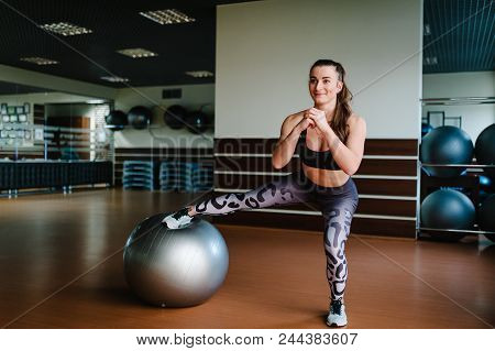 Beautiful Young Woman Stretching With A Pilates Ball In Fitness Gym And Doing Exercises With Fit Bal