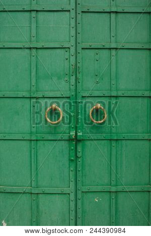 Large Antique Wooden Green Doors With Ring-shaped Handles.