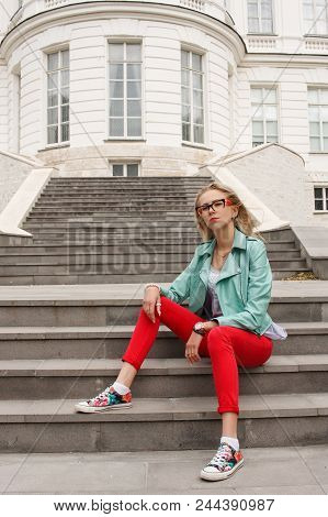 Beautiful Stylish Girl In Jeans And A Leather Jacket Sitting On The Stairs Near The Palace