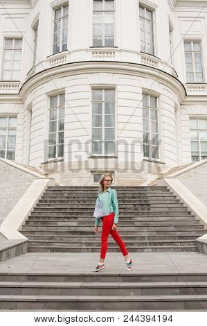 Fashionable Young Blonde Girl Posing On The Stairs. Stylish Woman's Look.