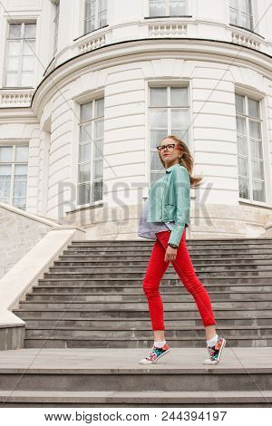 Fashionable Young Slim Blonde Girl Posing On The Stairs. Stylish Woman's Look.