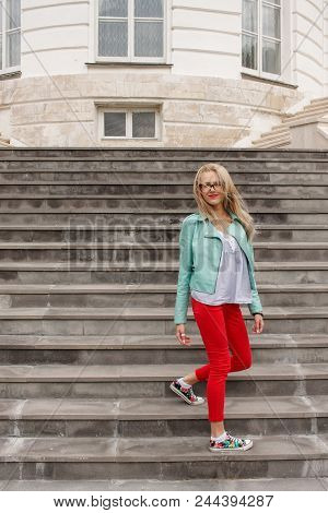 Fashionable Young Skinny Blonde Girl Posing On The Stairs. Stylish Woman's Look.