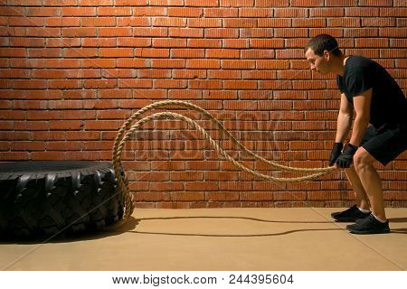 man performs an endurance exercise with ropes on a brick wall background poster