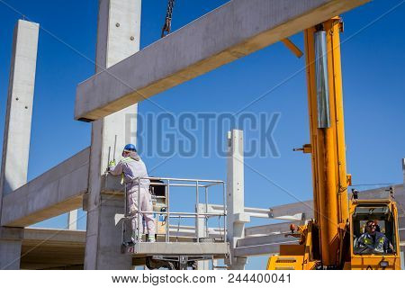 Worker is helping mobile crane to manage concrete joist for assembly huge construction. poster