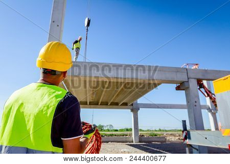 Worker is helping mobile crane with rope to manage concrete joist for assembly huge construction. poster