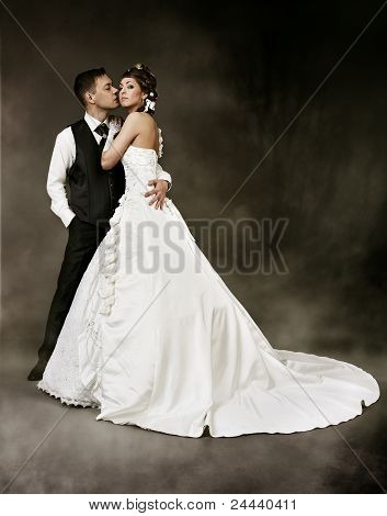 Bride And Groom At Dark Mysterious Background. Wedding Couple Fashion