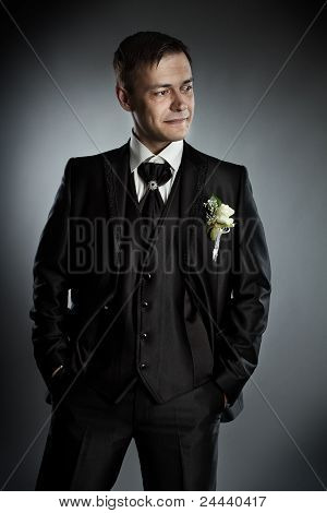 Handsome Man In Black Suit. Grey Background.