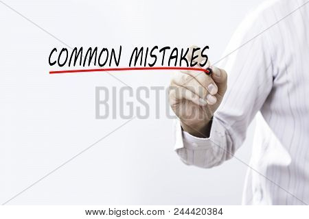 Businessman Draw Common Mistakes Word With Red Marker On Transparent Wipe Board, Business Concept. T