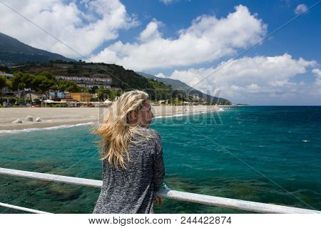 Blonde Woman Outdoor, Azure Blue Sea Background, Beach And Mountain In Sicilia, Italy