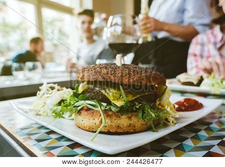 Cozy Restaurant Atmosphere With Delicious Vegan Burger In Cozy Restaurant Interior With Fries And Sa