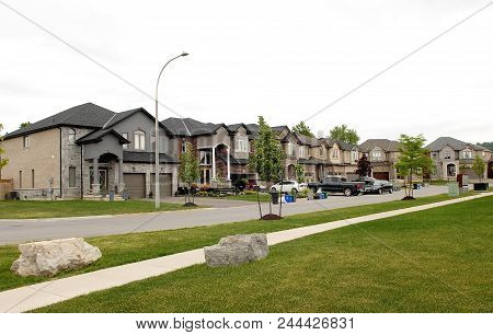 A Suburban Street With New Big Houses In The Summer Time Whit Cars In The Drive Way