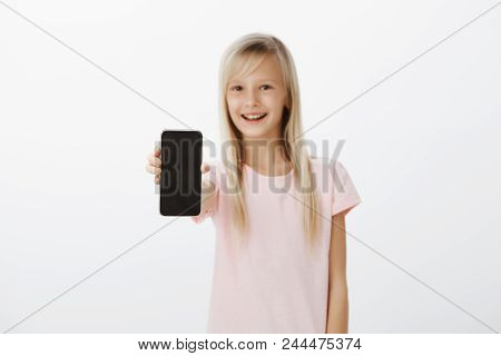 Upbeat Girl Showing New Mobile Phone To Friends. Happy Cute Child With Blond Hair, Pulling Hand With