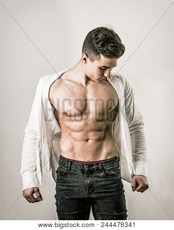 Handsome Young Muscular Man Shirtless Wearing Jeans, Taking Off White Shirt On Naked Muscle Torso, O