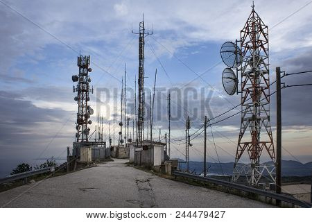 Plenty Of Radio Masts Located On The Hilltop Wit Antennas. Radio Masts And Towers Are Tall Structure