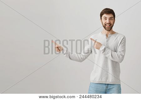 Happy Good-looking Caucasian Bearded Guy Pointing Left With Both Index Fingers, Smiling And Being Ex