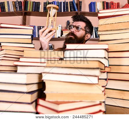 Man On Thoughtful Face Holds Hourglass While Studying, Bookshelves On Background. Teacher Or Student