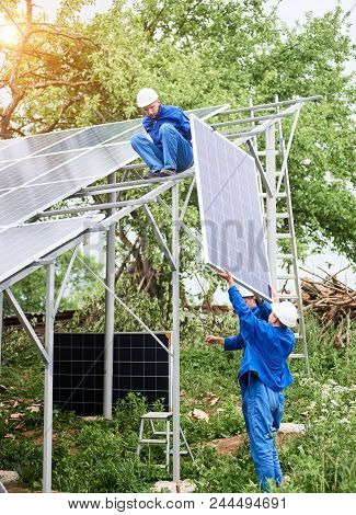 Installing of stand-alone solar photo voltaic panel system. Workers in hard-hats and blue overall lifting the solar module on metal platform. Alternative energy and professional construction concept. poster
