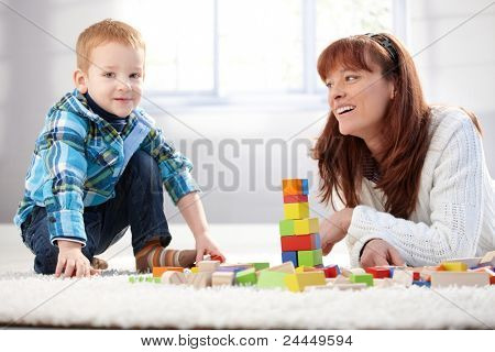 Mother and son building tower together at home, smiling.?