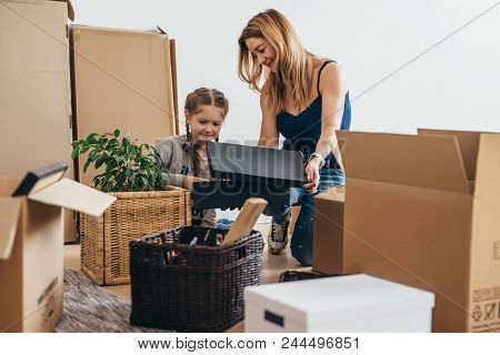 Family Unpacking Cardboard Boxes At New Home.