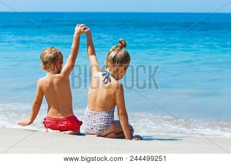 Happy Kids Have Fun In Sea Surf On White Sand Beach. Couple Of Children Sit In Water Pool With Hands