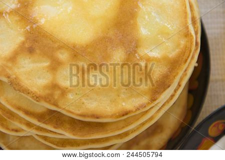 Tea In A Painted Cup, On A Saucer Sliced Lemon, Pancakes, Sour Cream And A Wooden Spoon For Overlayi