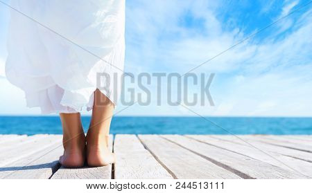 Beautiful And Healthy Feet Of A Young Girl In White Dress On A Wooden Pier. Sea And Sky Background.