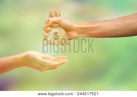 Man Hand Holding Money Bag And Giving Money To Another Person On Blurred Green Nature Background. Mo