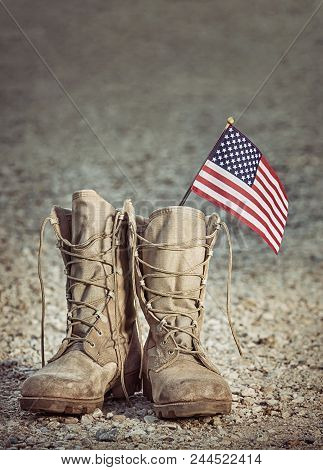 Old Military Combat Boots With The American Flag. Rocky Gravel Background With Copy Space. Memorial