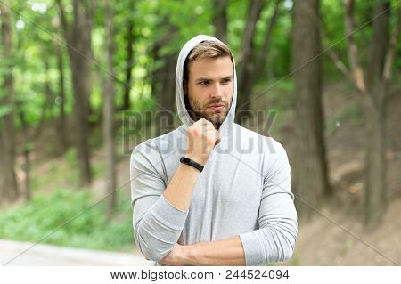 Sportsman training with pedometer gadget. Fitness tracker concept. Man athlete on pensive face with sport fitness gadget, nature background. Athlete with bristle with fitness tracker or pedometer. poster