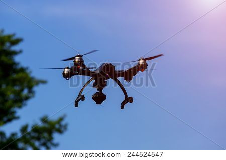 Drone Or Uav Flying Overhead In Blue Sky With Stabilised Camera