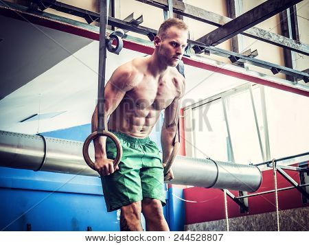Handsome Muscular Young Man Athlete Exercising In Gym, Hanging And Pushing Up With Rings. Tattoo Rea