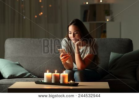 Relaxed Girl Using Phone In The Night With Candle Lights Sitting On A Couch In The Living Room At Ho