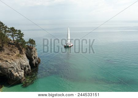 Panoramic View Of Pacific Ocean Blue Transparent Water, A White Sport Modern Luxury Yacht Sail Boat