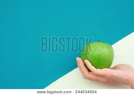 Young Caucasian Woman Holds In Hand Green Organic Apple On Duotone White Turquoise Background. Vitam