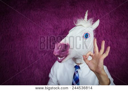 Freaky Young Man In Comical Mask Stands On The Purple Background. Portrait Of Unusual Manager. Funny