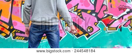 A Young Graffiti Artist In A Gray Hoodie Looks At The Wall With His Graffiti In Pink And Green Color