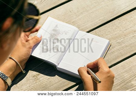 List Of Travel Concepts. Young Woman Writing In Notebook List Of Places To See