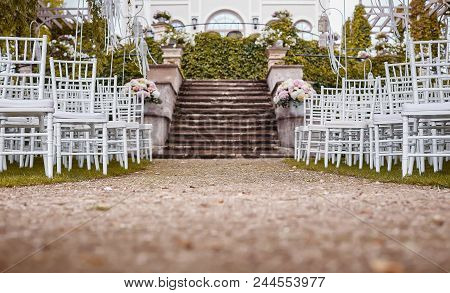Place For Wedding Ceremony With Wedding Arch Decorated With Flowers And White Chairs On Each Side Of