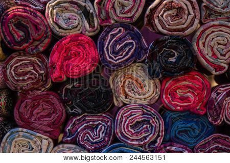 Colorful Rolls Of Fabric And Textiles In A Store Shop. Multi Different Colors And Patterns On The Ma